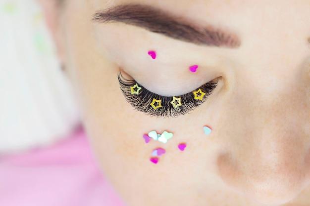 Le maître de l'extension de cils décore les cils de la fille avec des strass, des cœurs et des étoiles. extensions de cils créatives, maquillage des yeux.