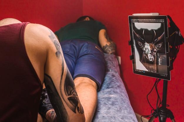 Maître faisant le tatouage en studio avec l'écran avec le projet