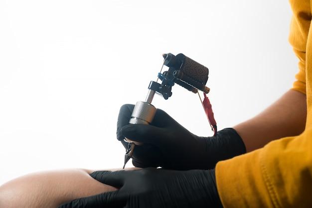 Le maître fait un tatouage sur la jambe de l'homme