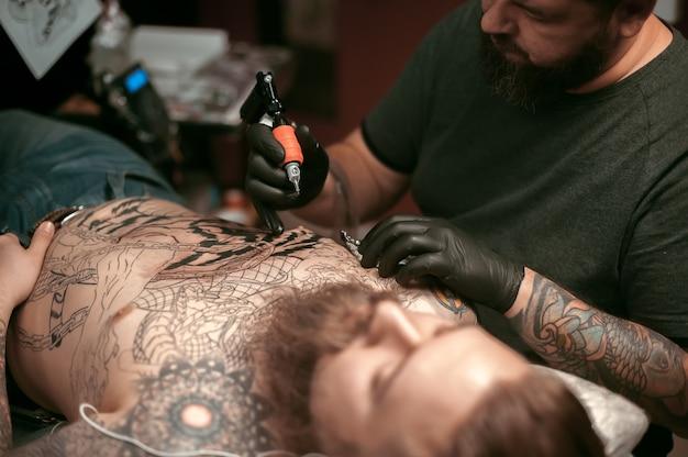 Maître fait un tatouage sur la peau de son client dans un salon de tatouage