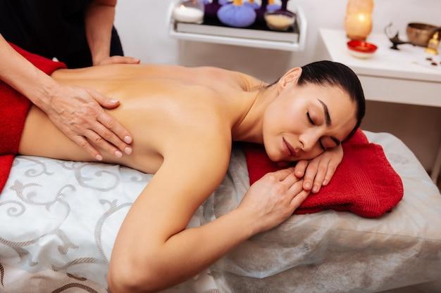 Maître de la guérison. femme agréable à moitié nue prenant une procédure méditative dans un salon spa pendant que le maître réchauffait son dos