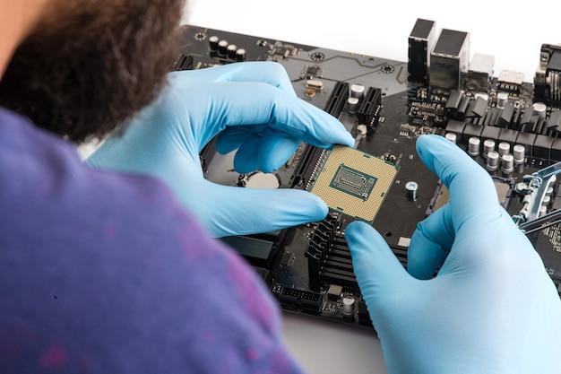 Le maître installe la puce du processeur cpu dans la carte mère en gros plan