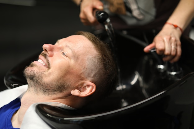 Maître lave la tête de l'homme dans l'évier du coiffeur