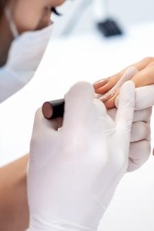 Maître de manucure dans des gants de protection appliquant du vernis à ongles beige sur les ongles féminins dans un salon de beauté