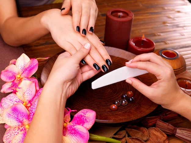 Maître manucure fait manucure sur les mains de la femme - concept de traitement spa