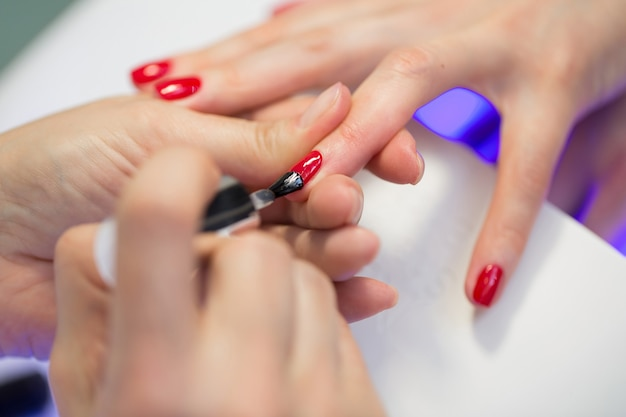 Le maître de manucure fait une manucure rouge sur la main de la jeune femme. maître des ongles femme faisant des ongles à une cliente dans un salon de beauté. prendre soin des mains