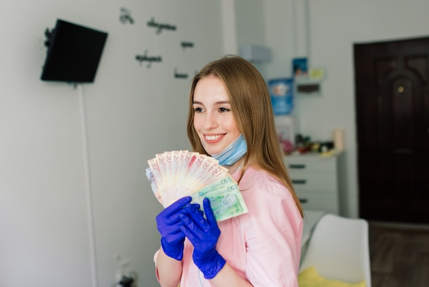 Maître de manucure féminine dans un salon de beauté avec masque de protection tenant de l'argent et souriant