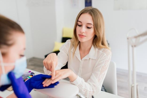 Maître de manucure féminine dans un salon de beauté travaille avec les mains du client