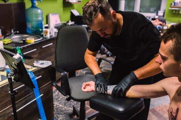 Maître mettant le projet de tatouage sur le bras