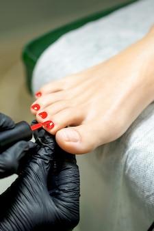 Maître de pédicure appliquant le vernis à ongles rouge aux ongles des pieds de la jeune femme dans un salon de manucure