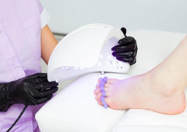 Le maître pédicure, après avoir appliqué du vernis à ongles violet, les sèche sous une lampe à ultraviolets. lampe pour sécher les ongles