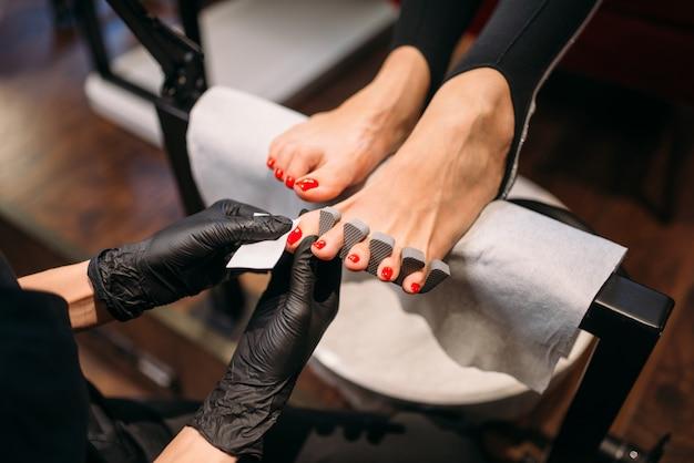 Maître de pédicure dans les gants polit les ongles avec une lime
