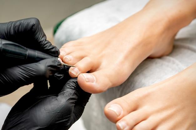 Le maître de pédicure enlève la cuticule des orteils d'une femme à l'aide de matériel à ongles électrique