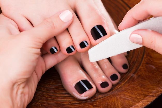 Maître pédicure fait pédicure sur les jambes de la femme - concept de traitement spa