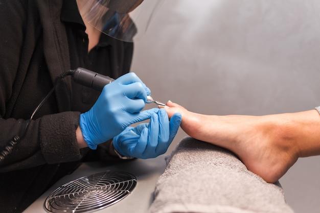 Le maître pédicure polit les ongles avec une lime à ongles avant d'appliquer la vue latérale du vernis