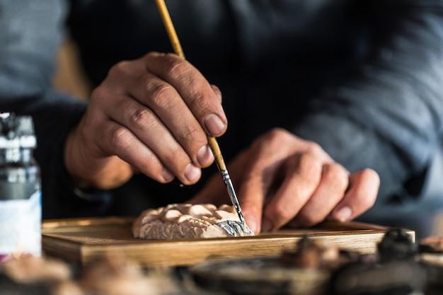 Maître peignant une sculpture de gesso. photo de haute qualité