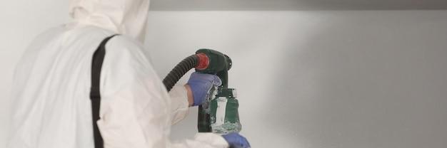 Le maître peintre en costume blanc peint le mur avec un pistolet