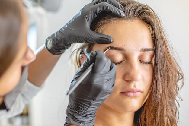 Un maître peintre des sourcils peint des sourcils en les colorant au henné. femme travaillant dans des gants noirs. architecture des sourcils