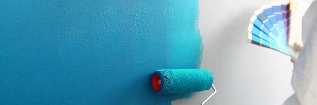 Le maître peintre tient dans ses mains une palette de couleurs avec des nuances de bleu