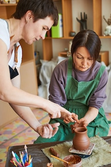 Un maître potier apprend à un élève à modeler l'argile.