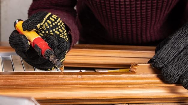Maître pour réparer un défaut sur une porte en bois à l'aide d'un crayon de cire et d'un fer à souder