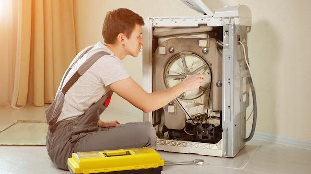 Un maître professionnel en pantalon de combinaison gris ouvre le panneau arrière du chargeur supérieur de machine à laver cassé par un mur beige en gros plan