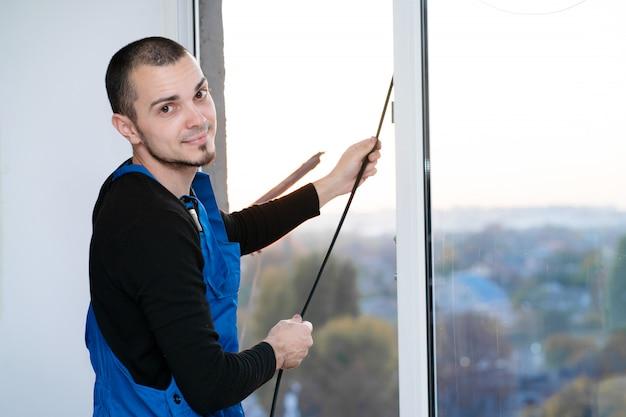 Maître professionnel à la réparation et à l'installation de fenêtres, change le joint d'étanchéité en caoutchouc dans les fenêtres en pvc