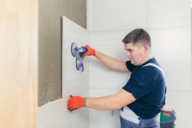 Maître professionnel travailleur masculin pose des carreaux de céramique sur le mur