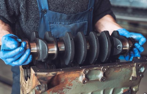 Le maître récupère un moteur reconstruit pour la voiture.