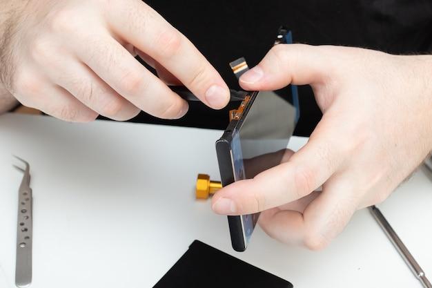 Le maître récupère un smartphone parmi les pièces du service de réparation de téléphone