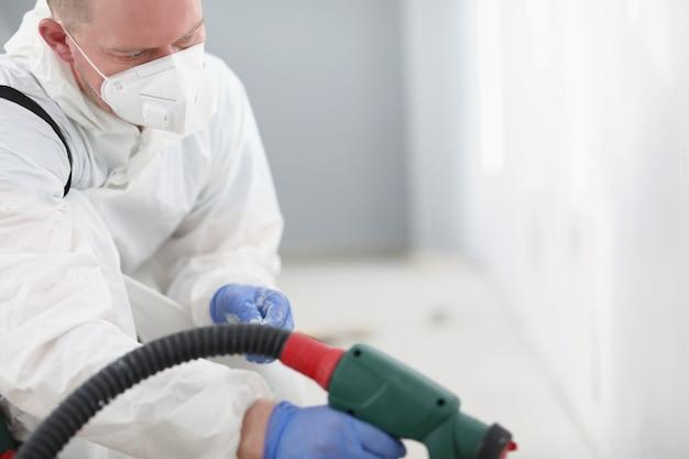 Maître réparateur en respirateur de protection et mur de peinture uniforme avec pistolet
