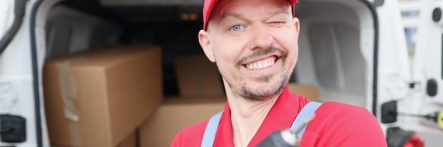 Maître réparateur tenant une perceuse électrique dans ses mains près de la voiture