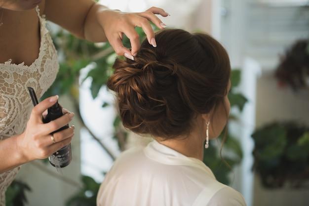 Le maître styliste fait la coiffure de mariage de la mariée