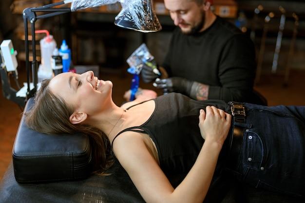 Le maître de tatouage caucasien barbu professionnel travaille dans un studio atmosphérique confortable
