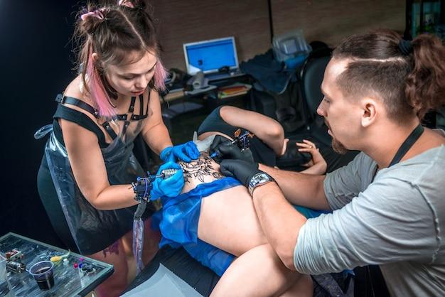 Le maître de tatouage crée un tatouage dans un studio de tatouage./tatoueur faisant de l'art du tatouage dans son salon.