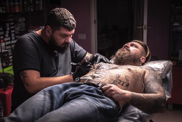 Un maître de tatouage fait un tatouage dans un studio de tatouage. / maître tatoueur montrant le processus de fabrication d'un tatouage dans le salon.