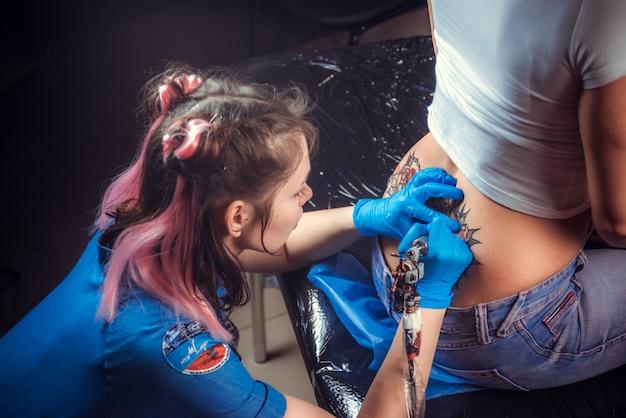 Maître tatoueur créant un tatouage dans un salon