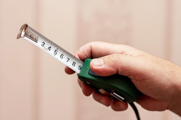 Le maître tient un ruban à mesurer dans sa main