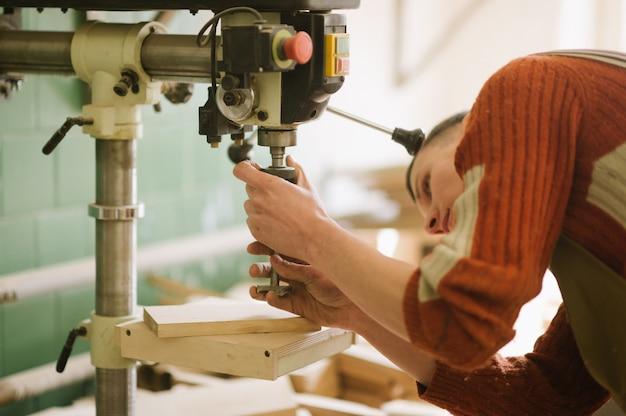Le maître travaille sur la machine à percer dans l'atelier de menuiserie