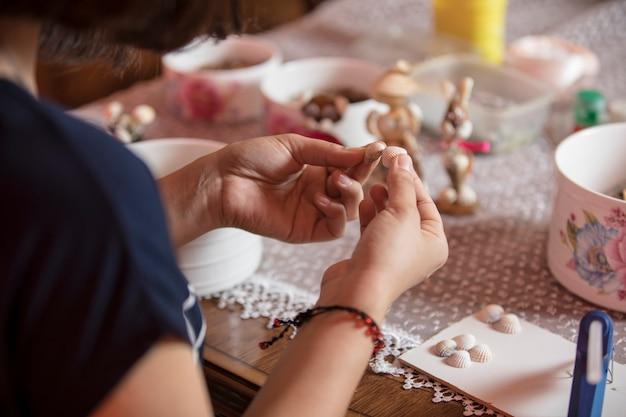 Maître en utilisant de petites épingles pour faire des décorations.