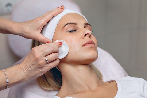 La maîtresse esthéticienne professionnelle efface avec un coton une grille dessinée avec un marqueur blanc sur le visage d'une cliente.