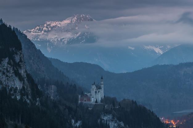 Majestueux château de neuschwanstein au crépuscule, entouré de montagnes