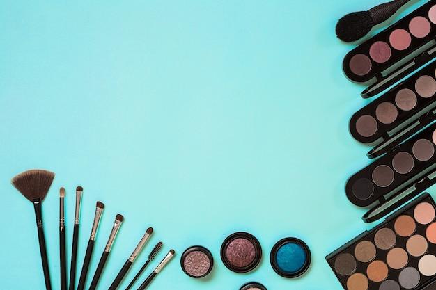 Make up essentials set de pinceaux de maquillage professionnels crèmes et ombres dans des pots sur fond bleu
