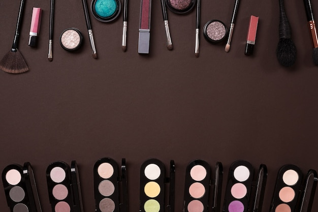 Make up essentials set de pinceaux de maquillage professionnels crèmes et ombres dans des pots sur fond sombre