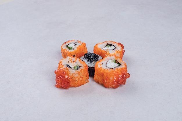 Maki et rouleaux de sushi de californie sur fond blanc.