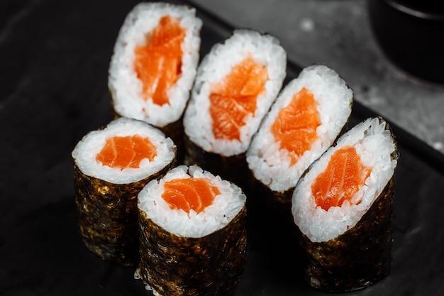 Maki simple au saumon frais. sushi sur fond gris.