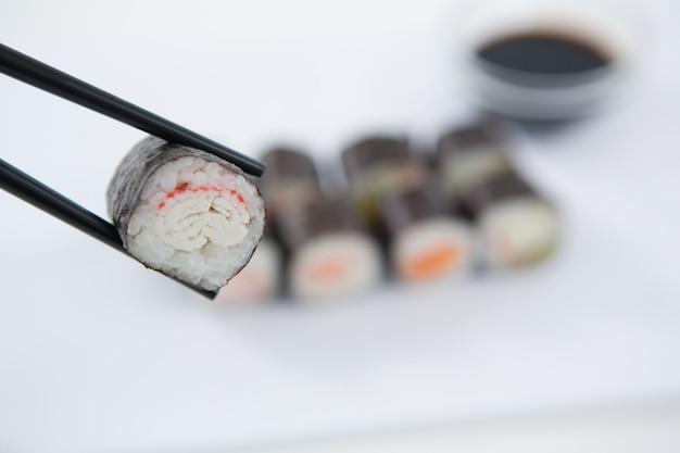 Maki sushi détenu dans des baguettes en bois