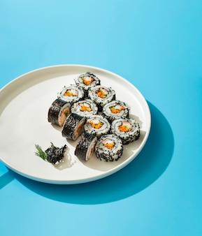 Maki sushi roule sur une plaque blanche