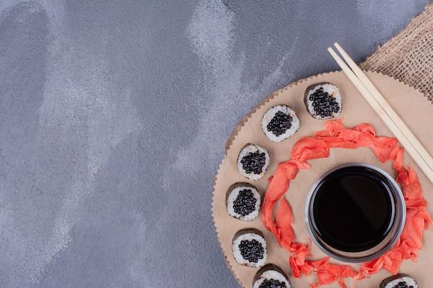 Maki sushi roule sur une plaque en bois avec des baguettes, du gingembre mariné et de la sauce soja.