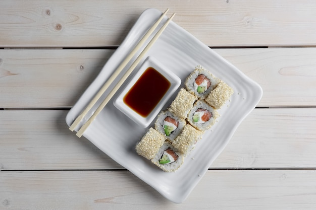 Maki sushi - rouleau avec saumon fumé, fromage à la crème, feuille de salade et avocat à l'intérieur. sésame à l'extérieur.